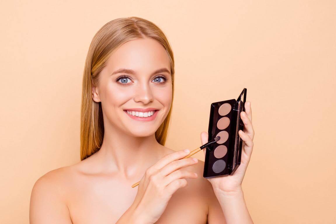 Junge Frau mit Lidschatten Palette- Thema: Augen schminken